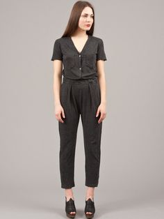 The work wear jumpsuit is cut from soft jersey with a V-neckline, front chest pockets, hip pockets and has an elasticated waist. There are front pleats from the waistline and a box pleat in the back.  The short sleeves are unfinished and the legs are slightly tapered.  50% Cotton, 50% Polyester.  Made in USA.Simona is wearing the 1
