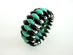 A gorgeous peyote ring! Made of Czech super duo beads in black and turquoise green and Japanese seed beads in silver lined crystal. The ring is