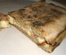 PANUOZZO PROVOLA E PANCETTA preparato con l'impasto della pizza cotto in forno, poi tagliato in due, farcito con provola affumicata, pancetta e successivamente ripassato in forno.