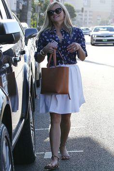 Reese Witherspoon wearing Thierry Lasry Angely Sunglasses and Valentino the Rockstud Reversible Textured-Leather Tote in Merlot.