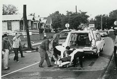 vintage ambulance being loaded after traffic accident