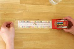 "Lay your label out on the table, and pull out a piece of packing tape just slightly longer (on each side of the label) than your paper.  You should also have just a tiny bit of tape above and below your paper (since the paper is 1 3/4"" tall and the tape is 2"" tall).  Press the tape smoothly onto the paper. Add to water bottle.  Target brand smooth bottles."