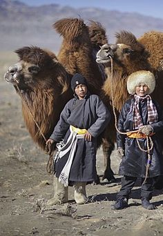 Nomads of Mongolia: An insight into their tribes, traditions and culture. Young nomadic herders, dressed in traditional attire, stand with their camels at Gobi Gurvansaikhan National Park, Ömnögovi Province. Religions Du Monde, Cultures Du Monde, World Cultures, We Are The World, People Around The World, Wonders Of The World, Around The Worlds, Camelus, Tribal People