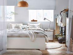 Ein helles Schlafzimmer mit einem großen ASKVOLL Bettgestell in Weiß, NATTLJUS Bettwäsche-Set in Beige und langflorigen ÅDUM Teppichen in Elfenbeinweiß