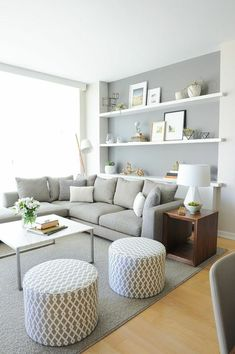 Light grey wall color with white shelves + hard woods in a palette including grey, white, black, and coastal artwork.