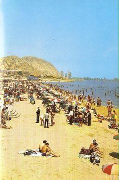 """1970. Playa de El Postiguet (Alicante). Al fondo valla publicitaria de la desaparecida cerveza """"El Nebli"""""""