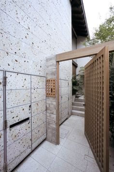 大谷石の外壁と木格子の門扉がアジアンリゾートな雰囲気のアプローチ
