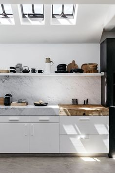 Kitchen with built-in butcher's block on the countertop, skylights, open marble shelf, thick marble countertop. Summer house in neutral tones design by Peter Ivens and Bea Mombaers