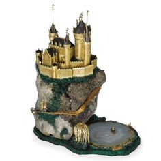 "An English Gold, Silver And Mineral Speciman ""Fairy Tale"" Castle, William Tolliday, London, circa 1980 mounted on a rocky mountain of rock crystal with pyrite inclusion, all on a faux malachite base, the many turreted castle of gold with oxidized silver roofs, complete with draw bridge, a knight in armor approaching on a serpentine gold path, strewn with diamond-set flowers, at the base a fisherman in a boat, floating on a striated agate pond with willow tree at one side signed on gold…"