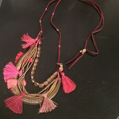 Anthropologie long tassel necklace Shades of pink and purple on a brown leather strand with gold chains and accents. From anthropologie. Was a gift but hardly ever worn!  Anthropologie Jewelry Necklaces