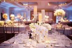 Rectangular and square tables with silver chivari chairs, textured white linens, crystal candle bases, creamy candle pillars, white orchids, lillies, and other varieties of white flowers.   A Four Seasons hotel wedding in Boston.