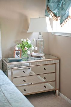For a clean, sophisticated look, try pairing items like this glamorous mirrored dresser with an elegant crystal lamp. They're both from HomeGoods - so are the pretty tulips!