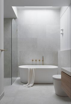 We used light light grey tiles with VJ wall Panelling to create this calming Coastal bathroom. Round wall lights add interest and balance, whilst the brass tapware adds warmth. The space is filled with natural light from a skylight centered over the bath. For more of the latest design tips, trends and products, follow us on Instagram and Pinterest. Light Grey Bathrooms, Grey Bathroom Tiles, Coastal Bathrooms, Bathroom Plans, Bathroom Tile Designs, Bathroom Design Luxury, Laundry In Bathroom, Bathroom Layout, Modern Bathroom Design