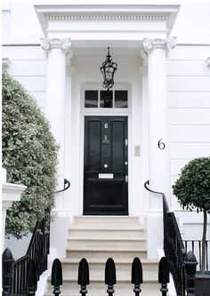 Love the color combo of black door/fixtures, white surround and light stone
