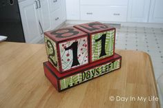 Christmas countdown blocks {Supplies needed: 4x4 inch wooden blocks, 1x4x5 inch wooden stand, 3 patterned scrapbook papers, numbers & 'days left', red & black paint, mod podge}