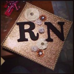 Nursing school graduation cap decorated! RN! I used a large square piece of glitter paper ($1.99), 2 cardboard letters (.99 each), a pack of flowers ($4.19), and 4 strips of pearls with sticky backs ($1.99 per pack of 3). All items from hobby lobby! I decorated the piece of paper, then hot glued the whole thing onto that hat!  The black button for the tassel is under the small flower in between the R & N :)