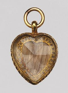 In this example, a faceted crystal was secured to the gold back by a crimped, scalloped edge. Beneath the glass, a tightly woven plait of light brown hair was laid onto a silk background. The locket is inscribed on its reverse with the death date of the deceased: obt 20 / of April / 1706 above an engraved skull.