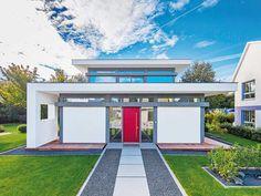 Hier sehen die Gäste Rot – die Haustür ist gigantisch inszeniert. Ein Weg aus Überformat-Platten im Kiesbett führt  geradewegs auf das mittig im Gebäude platzierte, überhohe Bauelement zu. www.flock-haus.de