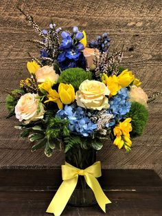 A beautiful arrangement with roses, tulips, blue hydrangea, heather, freesia, green dianthus, and delphinium.