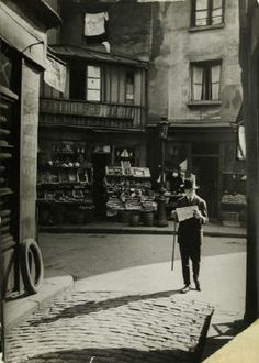 Man walking with cane, reading newspaper, c.1920.