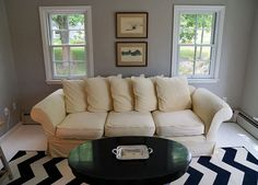 Living room with white couch, black round coffee table, silver tray, black and white chevron throw rug and classic accents.