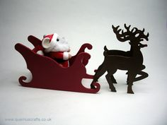 Santa Mouse, made by Quernus Crafts, is sitting in a hand-painted wooden sleigh created by JS Miniatures.