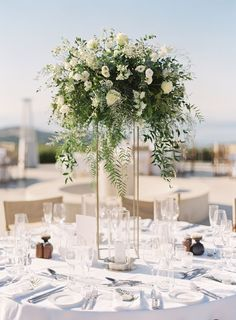 Tall centerpieces by towered over the tables. The transparent vases showcased white roses, white lisianthus, and greenery. Simple Wedding Centerpieces, Wedding Flower Arrangements, Floral Arrangements, Floral Wedding, Wedding Colors, Wedding Flowers, White Roses Wedding, Geometric Wedding, Purple Wedding