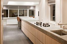 The Living Kitchen B.V. by Paul van de Kooi. Massief eiken houten fronten, ter plaatse gestort betonnen blad. Pitt Cooking kookplaat, MGS kraan in RVS uitvoering, RVS onderbouw spoelbak