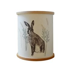 A Northern Light Hare Candle Cover: These tealight candle covers by A Northern Light feature Claire's beautiful illustrations. This one shows a hare in grasses. It is made from parchment paper that creates a warm glow when lit. The paper is backed with a UV stable, flame-retardant PVC, which also helps to diffuse the light and is kept in shape by two wooden embroidery rings.