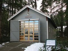 Converted barn or garage door idea with swinging barn doors and a full glass bay door