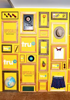 A bold yellow press wall included framed logos and objects evocative of an upscale lifestyle—such as a fedora, a bow tie, sunglasses, and a globe.