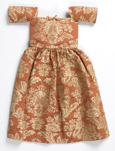 Child's Dress, United Kingdom, early 18th century. Red silk damask with floral pattern in white. Bodice cut square at neck and edged with pink ribbon