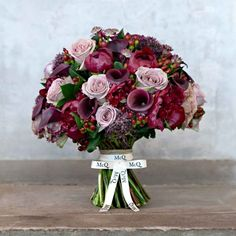 Ripe with red hypericum berries, burgundy callas and deep red peony, the pink Ocean Song roses in this bouquet provide the perfect counterpart to these rich, red tones...