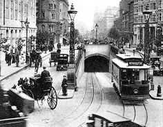 Kingsway Tram Tunnel, Holborn, London. In the foreground, a trolley on the tracks as well as cart, car, and foot traffic.