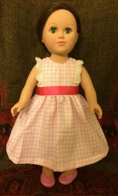 American Girl doll dress. From the Miss Bo peep collection. Long, pink, hounds tooth design dress with lace details on sleeves and pink bow accent around waistline.