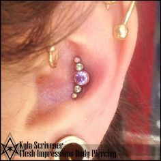 Conch piercing I updated with an Anatometal cluster. Stones are Amethyst, Peridot and White Opal in an anodised rose gold/copper setting.