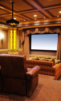 "This home theater is designed in a very traditional ""theater"" style. The projector screen is tucked behind a set of thick velvet curtains, and the custom coffered ceiling, paired with the ornate wall details and mirrored entrance doors give this room a great atmosphere. The room has two levels: the lower level has a long sectional sofa, while the back has nail-head-trimmed recliners."