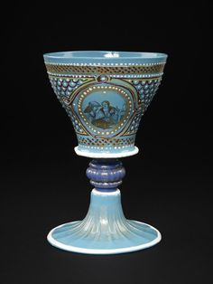Goblet of turquoise opaque glass decorated with enamel and gilding; cup flares outwards at the rim. The body painted with scale work in dark red with white dots; on each side, within an elaborate ogival frame, is a medallion enclosing a pair of lovers, a man and a woman as if seen by day and by night. Italy (Venice), late 15th century.