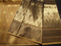 Description  Type: Multi-Purposes, Crafting  Color: Brown Gold  Brand: Three Students  Pattern/Style: Thai Pattern  Material: 	Silk Synthetic Fabrics  Width: Greater than 60''  Length/Amount: 1 - 2 yds  Country of Manufacture: Thailand  Conditions : Brand New  Suggestions  -...