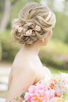 Tranças presas e entrelaçadas com fitas, um toque clássico e elegante no penteado para a cerimônia de casamento.