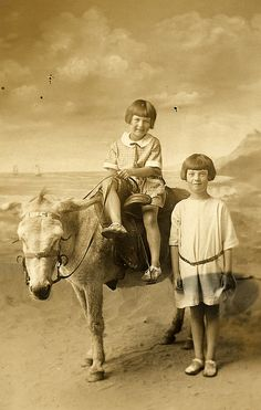 Joyce and Nora at Skegness in 1925. Found image. This photograph is unusual because in most seaside photographs with ponies and donkeys the children do not look as though they are enjoying themselves. I like these girls's period dresses, sandals and hairstyles. Interestingly the donkey has a sidesaddle. I am uncertain whether at this date the sidesaddle was still thought more suitable for ladies. Vintage photo.     Courtesy: LovedayLemon. Norwich, England (UK).