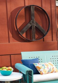 Turquoise metal bench (glider?!), BIRD PILLOW!, and peace sign--GET IN MY BACK YARD, please!