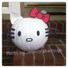 DIY hello kitty pumpkin. Project cost was less than $5. pumpkin was $3.88. White, pink & black construction paper. We used the cheap white spray paint for .97 cents at Walmart. Hot glue to glue on the piece. My husband cut out triangles for the ears then folded them inward to make it curve. He free handed the pieces from a picture on google images.