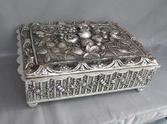 Caixa porta jóias, metal espessurado a prata, tampa decorada com flores e frutos. Estilo neoclássico. Dobradiça com defeito. 11 x 28 x 22cm.