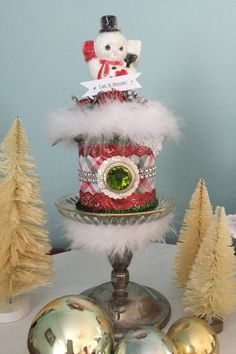 "This festive decoration was made from a glittered snowman (mid century), sitting atop a red ribbon spool, and surrounded with plenty of sparkly berries and miniature ornaments.  All displayed on a vintage sliver candle holder - so jolly!      This handmade and one-of-a-kind creation measures approximately 9 1/2 "" tall and 5"" wide 