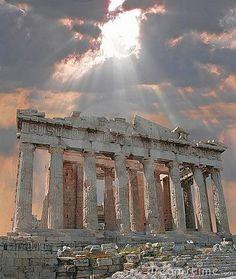 Sun bursting through the clouds over the Parthenon Acropolis in Athens, Greece
