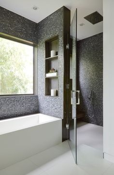 Dark gray mosaic tiles from Ann Sacks to create warmth in this modern white bathroom. #whitebathrooms