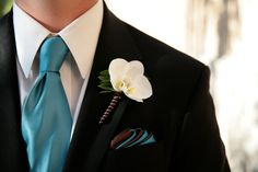 Turquoise necktie and orchid boutonniere.