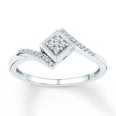This contemporary promise ring for her entices with a cluster of diamonds dancing around the sparkling central diamond. Twists of diamond-studded sterling silver form the band to complete the spellbinding design. The ring has a total diamond weight of 1/8 carat. Diamond Total Carat Weight may range from .115 - .14 carats.