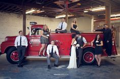Anna Lee Media, Oklahoma wedding photographer, red fire truck wedding prop, industrial wedding decorations, warehouse, garage, bridal party pose, bridesmaids, groomsmen, bride and groom, firefighter wedding, wedding dress, black sash tie, groom hat